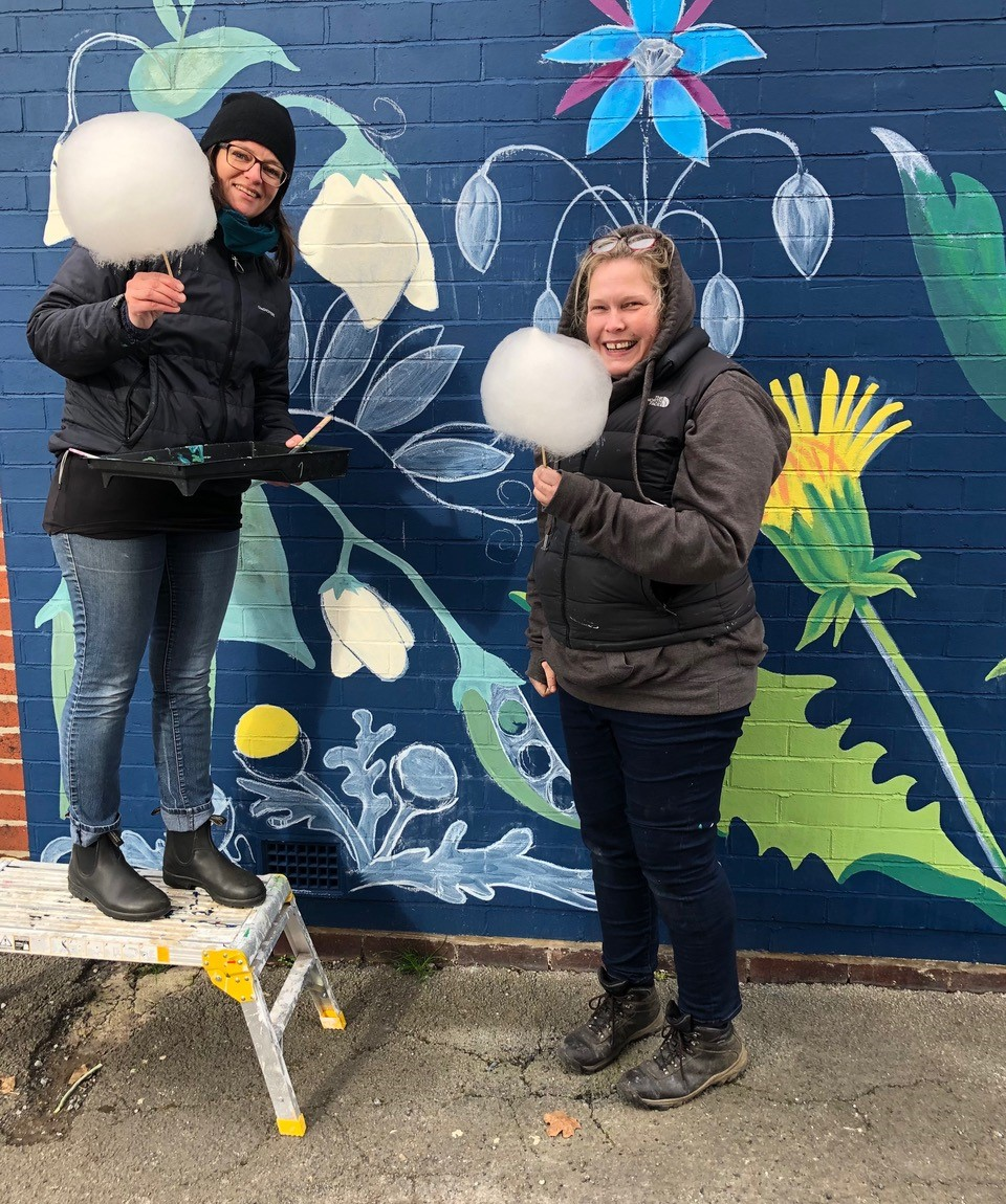 Artists holding candyfloss in front of the mural