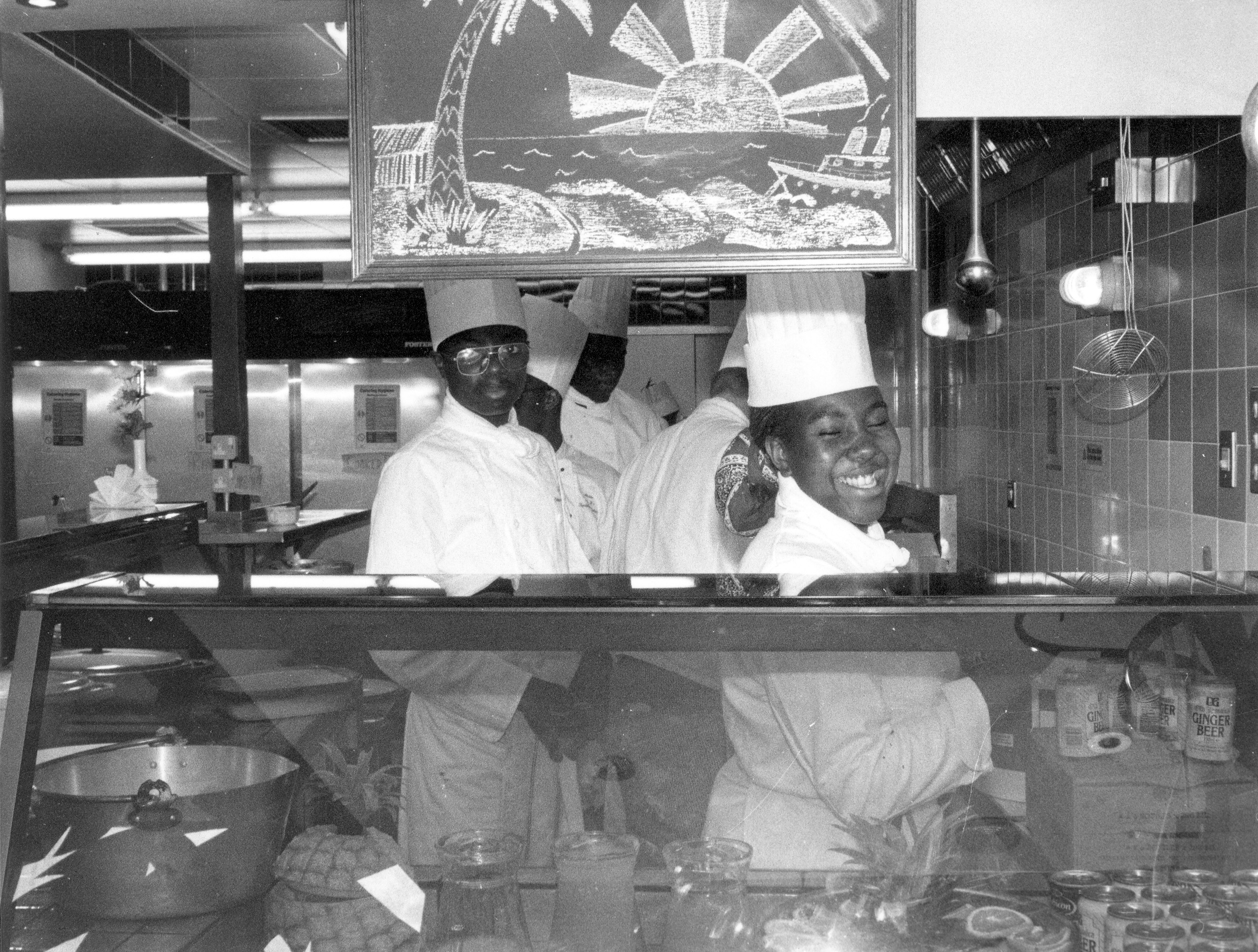 black and white photo of staff behind the counter of Dr. B's Caribbean Restaurant in 1980s