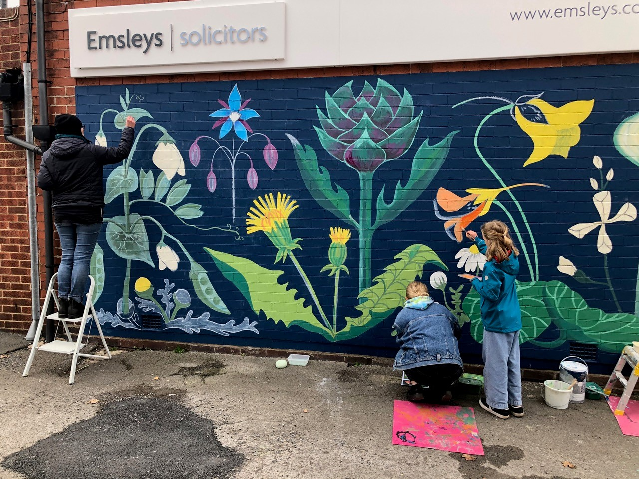 A family helping to paint the mural