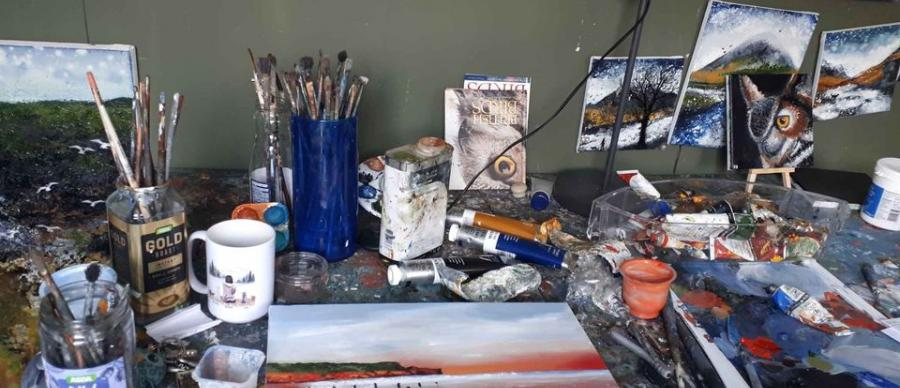 A collection of artist materials including oil paints, canvasses and brushes