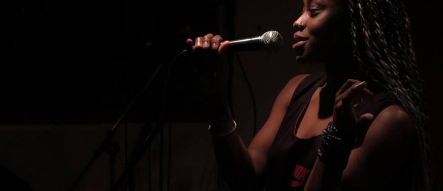 Rheima Robinson from Sunday Practice holding a microphone.