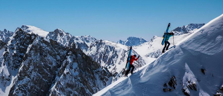 Skiers climbing a snowy mountain on a sunny day