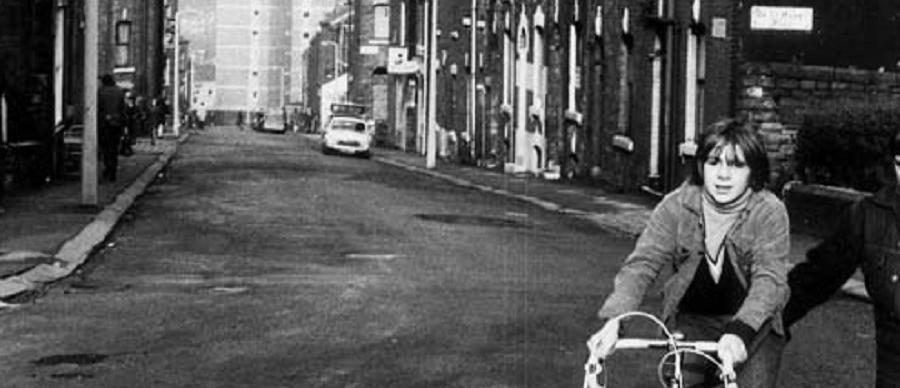 Boy on bike in 1970s Leeds street of back to back terraced housing
