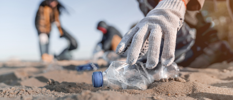 Gloved hand reaches for empty plastic bottle on the beach