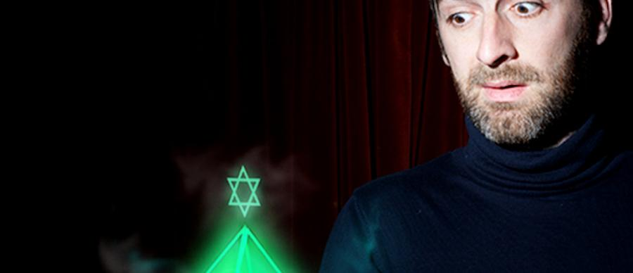 A man in a black polar neck is holding a hologram of a green glowing pyramid with a star of David