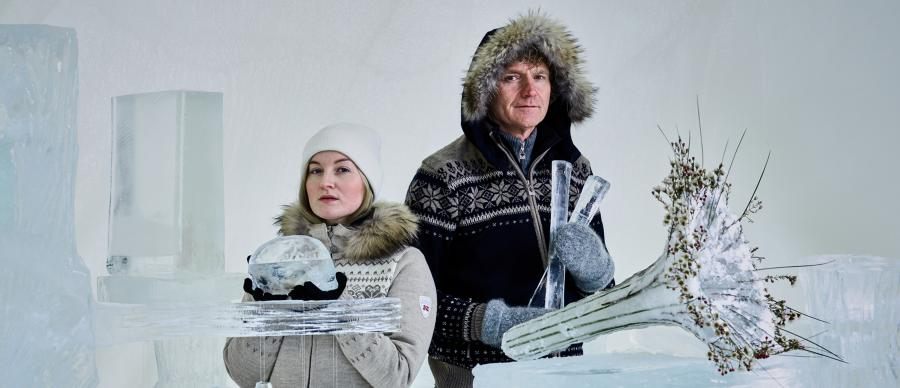 A man and a woman dressed in fur-lined woollen clothes surrounded by objects made of ice