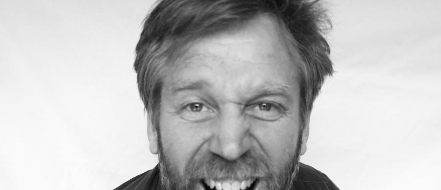 Tony Law in black and white grinning into the camera