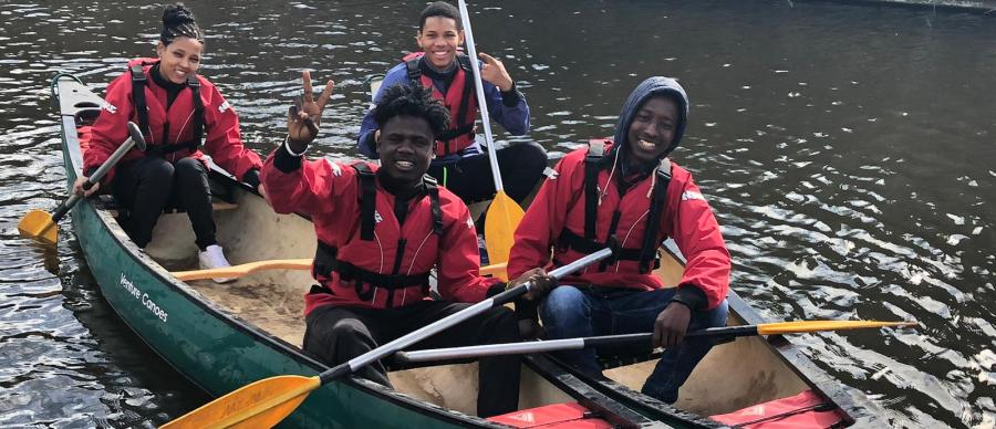 Four young people in life jackets, smiling on canoes