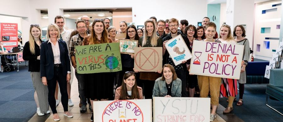 Group of students gathered ahead of a climate strike march holding plackards