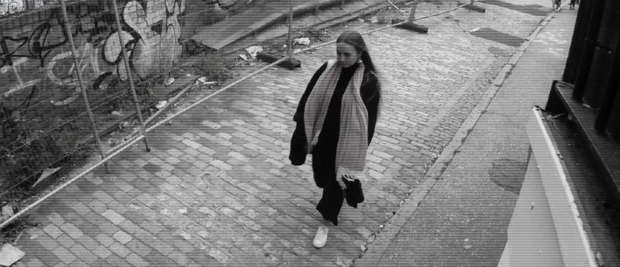 picture shows a woman walking down a street in black and white