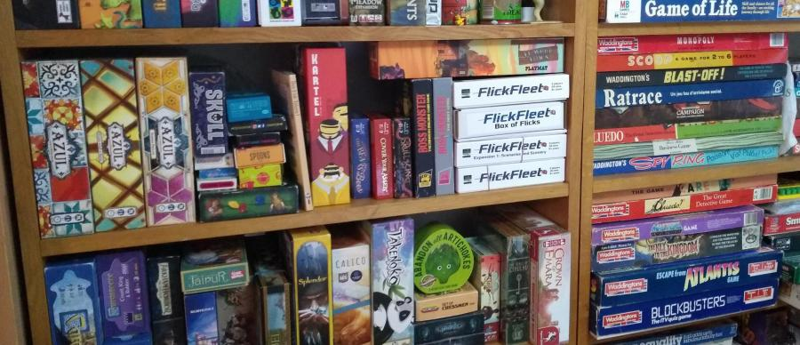 Bookshelves with a selection of board games both modern and retro.