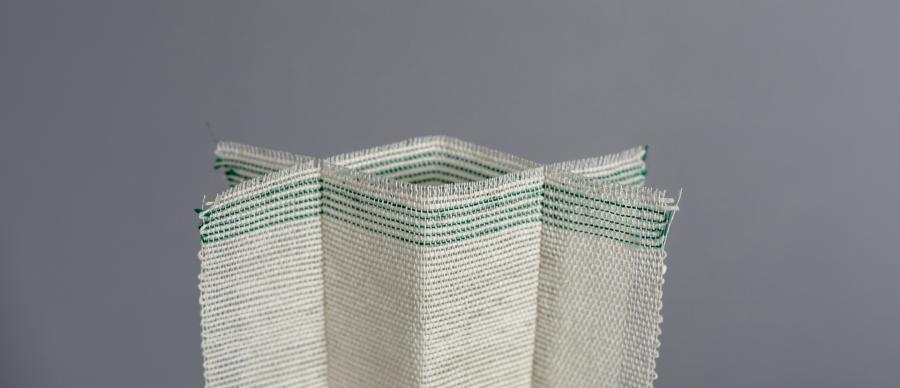 A pale cream woven form  with green thread on grey background