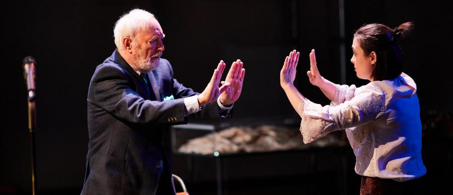 Two people stand with arms outstretched mirroring each other, one older and one younger