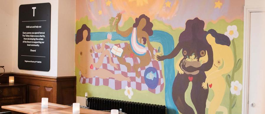 A brightly coloured mural with dancing naked people around a picnic blanket. The mural is painted on