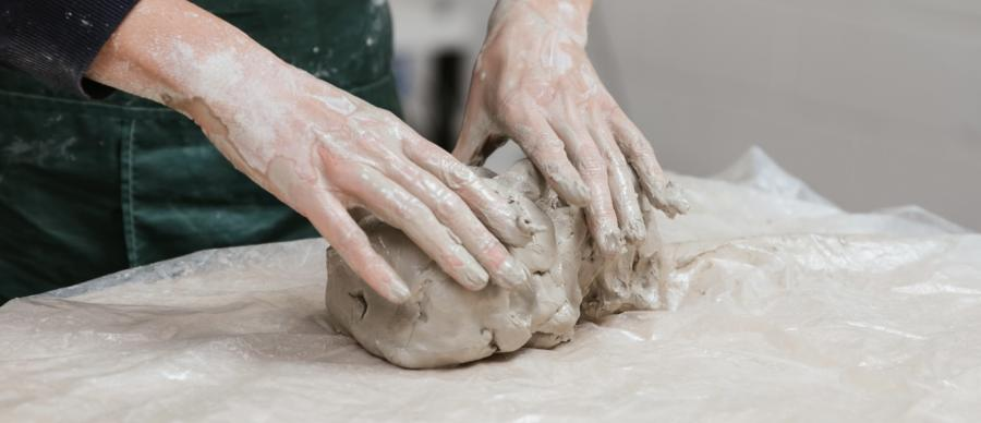 Clay covered hands holding a lump of clay covered in slurry