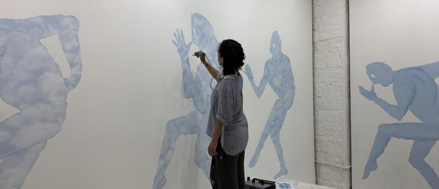 An artist working on a mural in a room