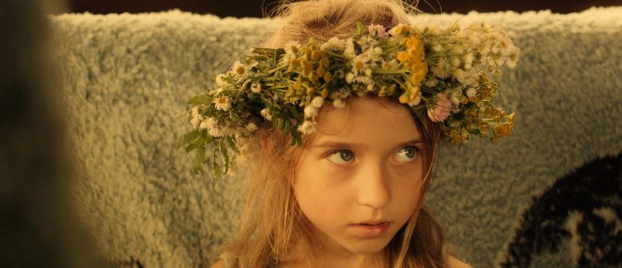 Close-up of a young girl wearing a flower crown.