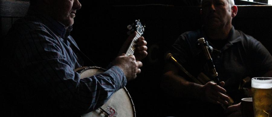 two men in a pub playing Irish Music in shadow