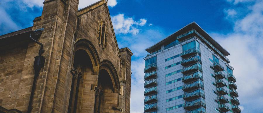 Leeds Cathedral next to a new high rise building with blue sky