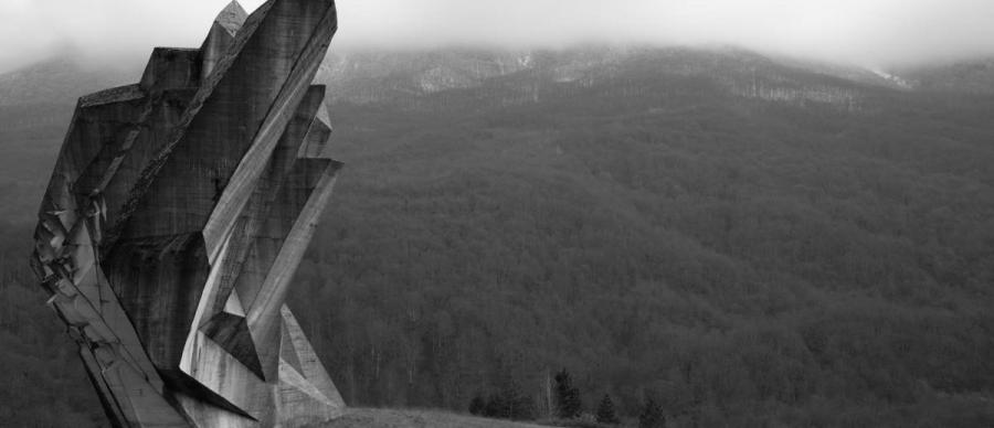 an outdoor monument in black and white with forests behind
