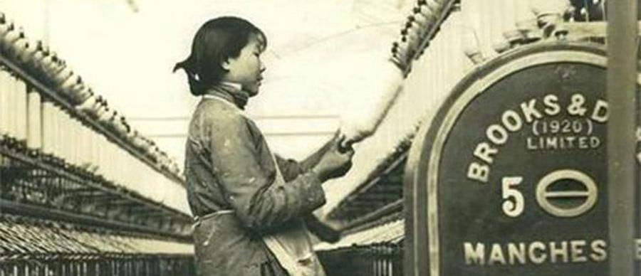A female textile worker in Shanghai is working on the looms in a black and white photograph
