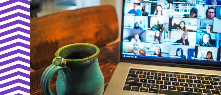 Photograph of a cup in the foreground and a laptop in the background.
