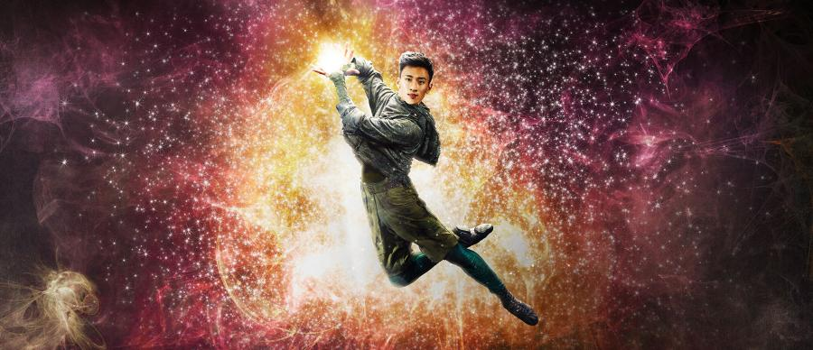 A male ballet dancer leaping in the air. In his hands there is a glow of magic.