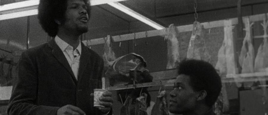 Two men with afro hair stand in a butchers - one is stood holding a cup.