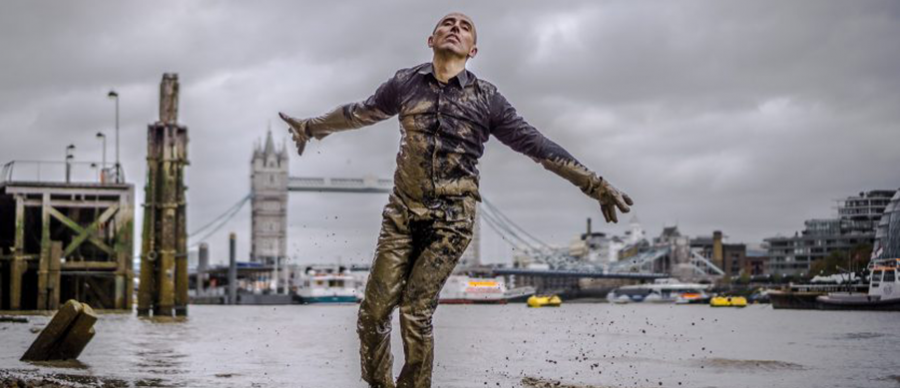 Male dancer stands covered in mud on the banks of the river thames.