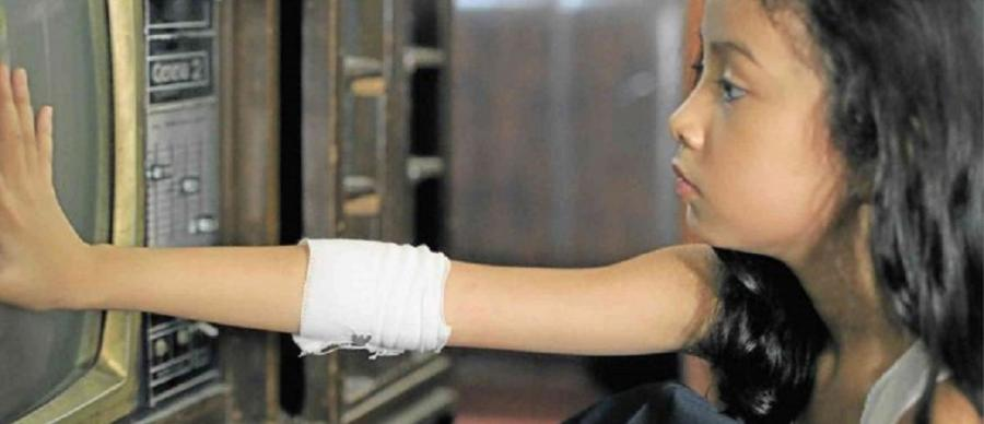 A small girl with a bandage on her arm presses her hand agains the screen of an old style TV