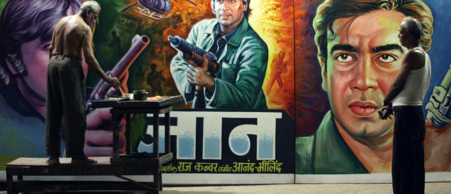 Original Copy Film Still - Artist paints Indian film poster on a wall whilst another man watches on.