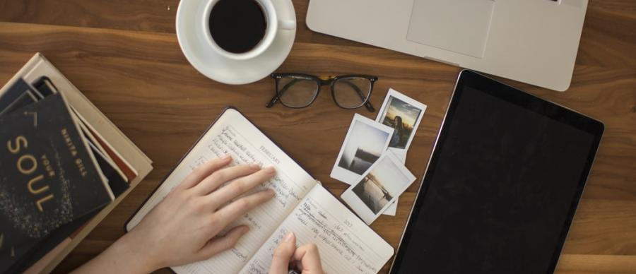 a desk with diary, coffee, laptop, hands holding a pen, books