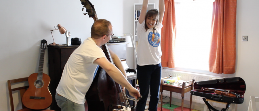 Megan is jumping and smiling as James improvises on the double bass.
