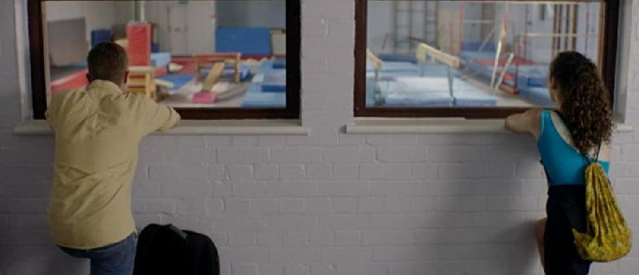 Two teenagers look through windows into a gymnasium