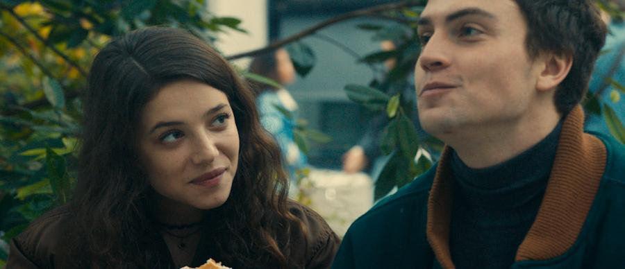 A young woman is looking lovingly at a man whilst eating