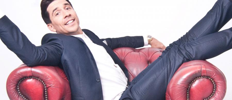 Russell Kane sitting on a red chair