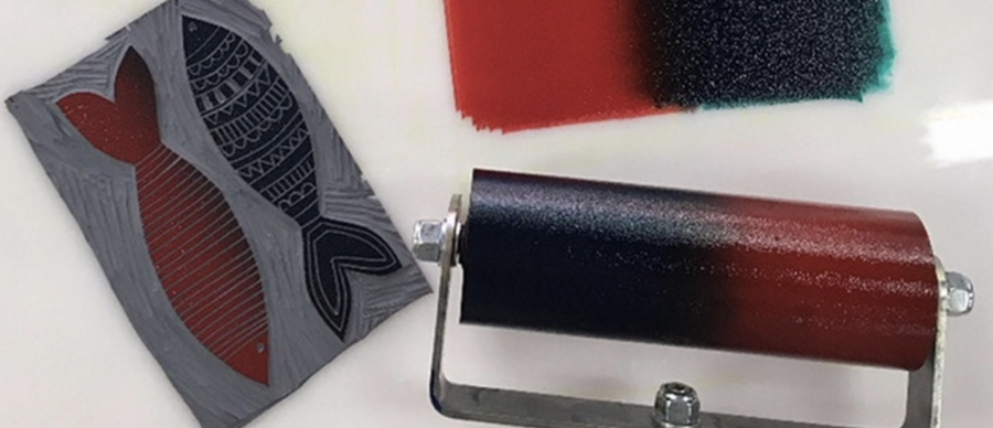 Image of a roller covered with ink and a linocut fish design ready to print