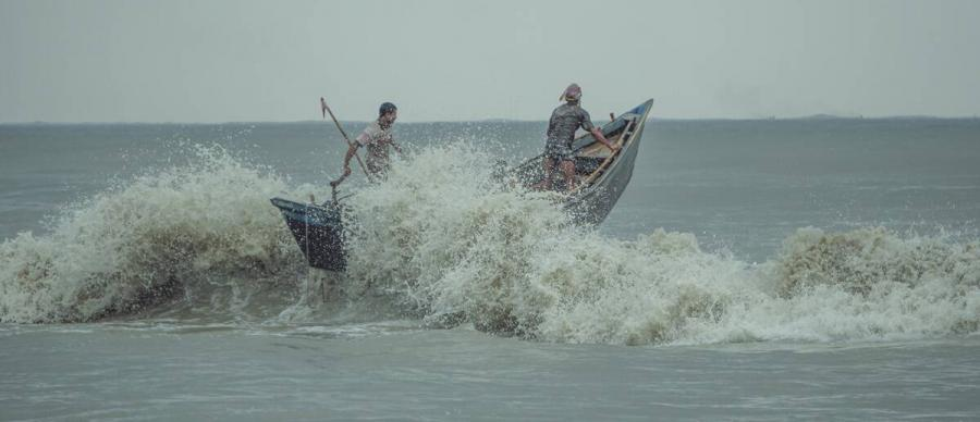 The Salt in Our Waters Film Still. Two men in a small boat pushing against a wave.