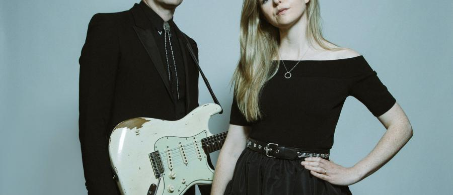 Band members posing with an electric guitar in front of a light backdrop