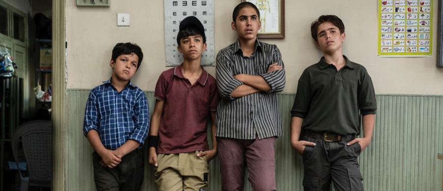 Four boys lean against a school wall
