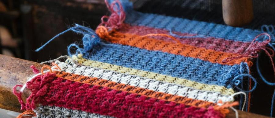 A close up of blue, orange and red woven fabric on a wooden loom