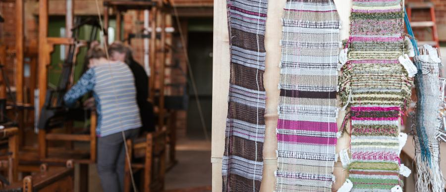 3 pieces of woven fabric hung on a wooden board and two women operating a weaving loom