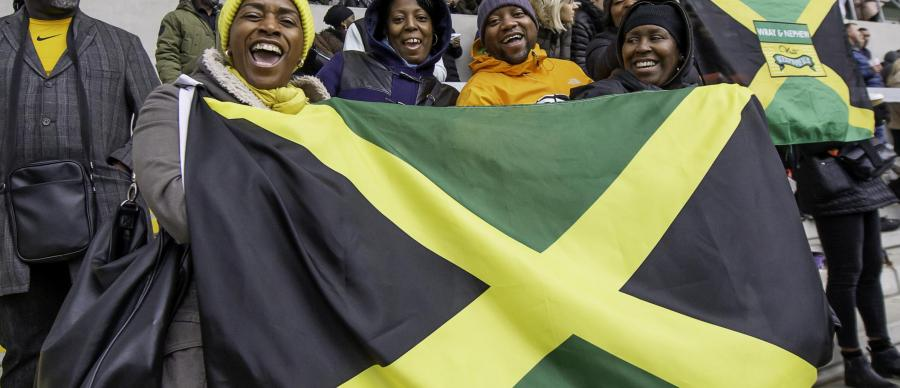 Picture of Jamaican fans holding a Jamaican flag at a Rugby League match