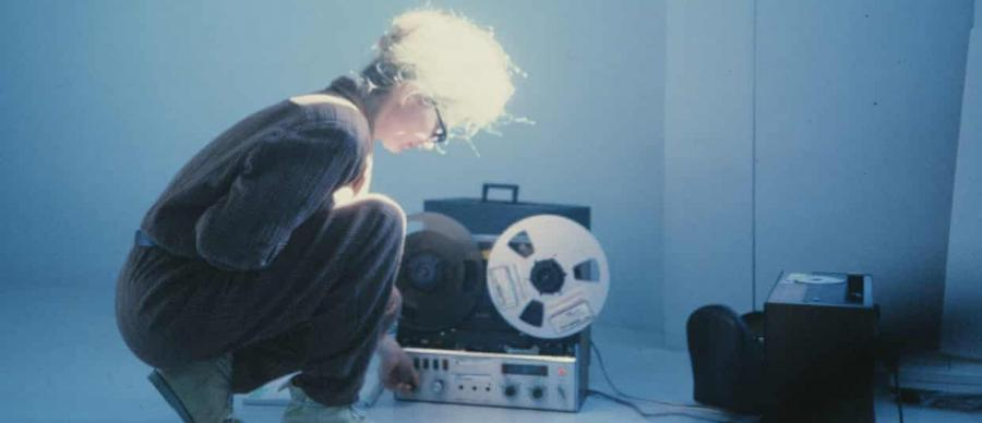 Sisters with Transistors Film Still. A woman bends down over an old tape recorder.