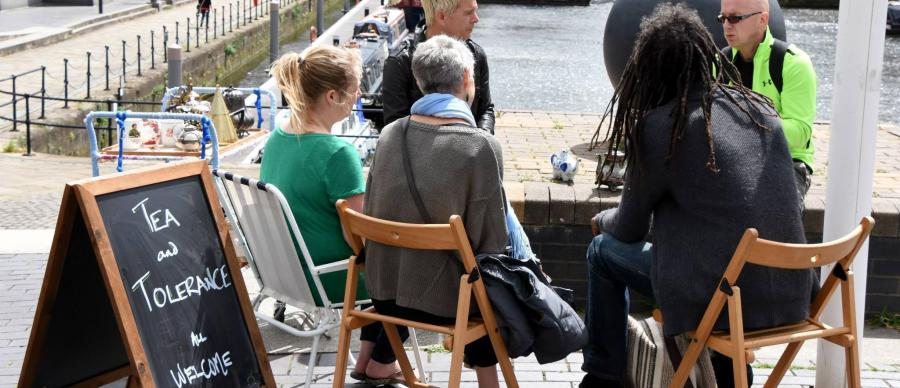 A group of people sat around a table outdoors deep in conversation