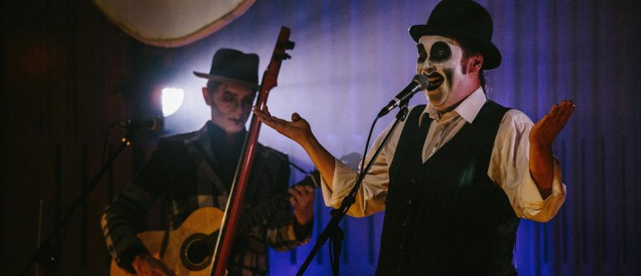 Two men in black and white skull facepaint and bowler hats, one playing guitar, on a darkened stage