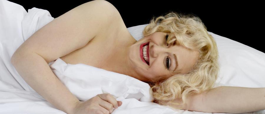 actress playing Marilyn Monroe laying on a white sheet