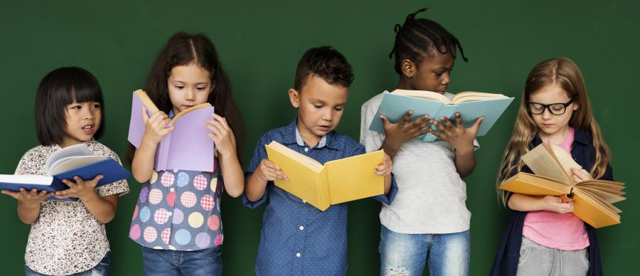 5 children of various genders, ages and ethnicities all standing reading books held in front of them