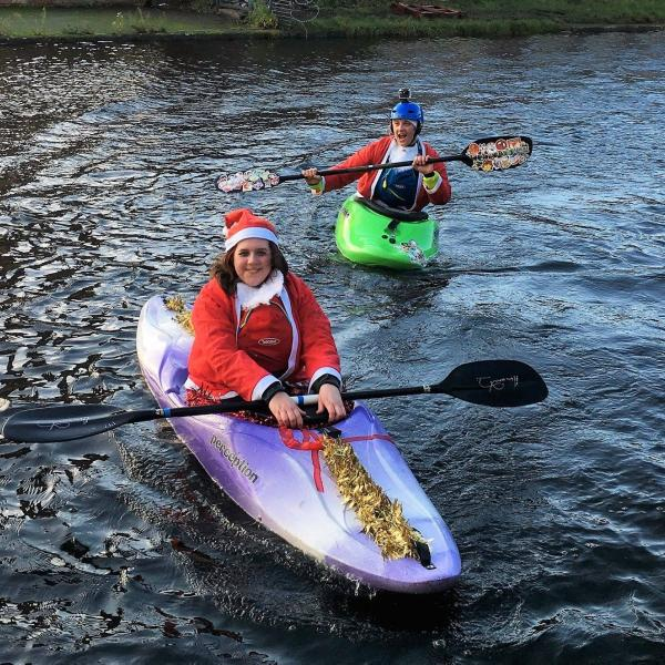 Person wearing a santa suite sat in a kayak on the canal