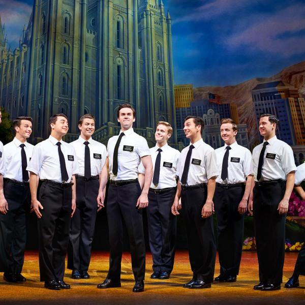 The cast of The Book of Mormon - an ensemble all wearing white shirts, black ties and badges.